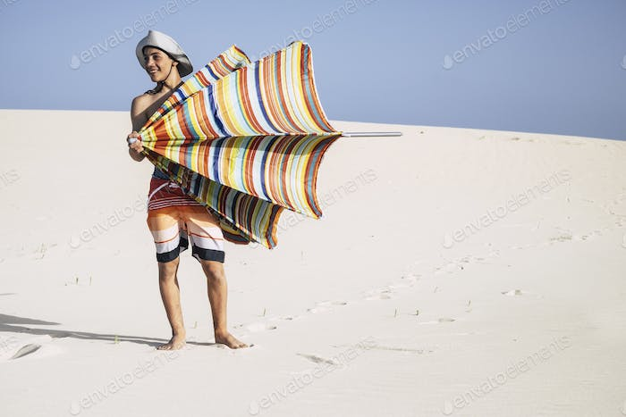 handsome tourist teenager boy caucasian cheerful and have fun enjoying the umbrella sun
