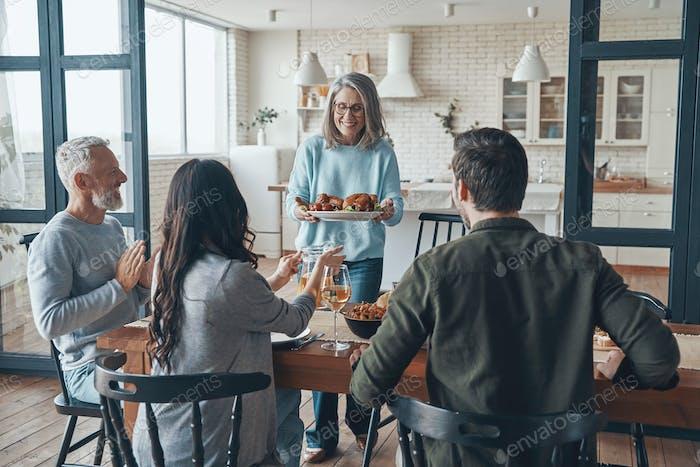 Modern multi-generation family smiling while having dinner together