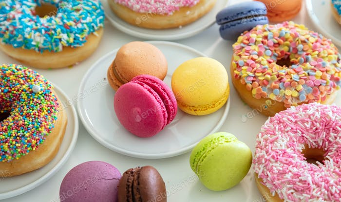 Donuts and macarons on wood, close up view with details