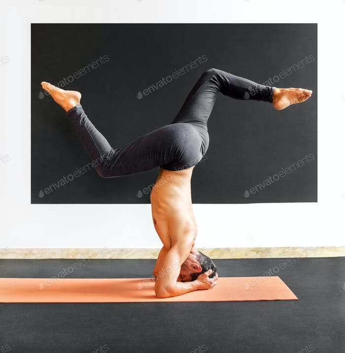 Man doing a sirsasana variation yoga headstand