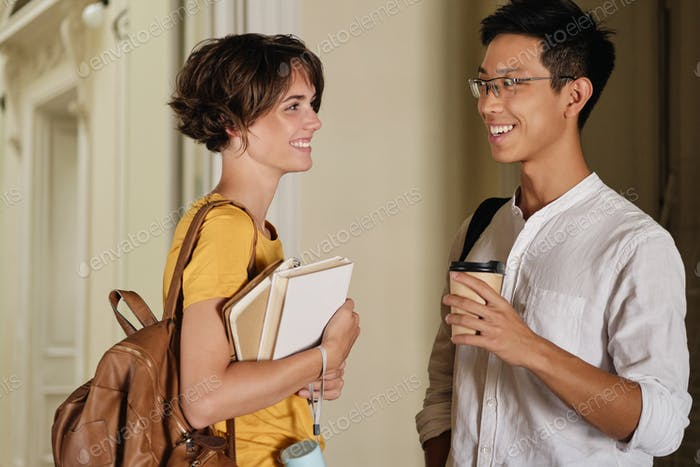 Two young attractive smiling international students joyfully talking in corridor of university