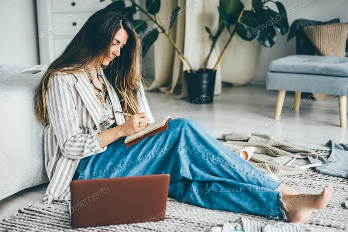woman  writes in paper notebook sitting on floor near laptop at home.