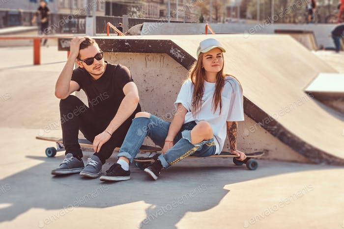 Young trendy couple are sitting at sunny skatepark with their longboards