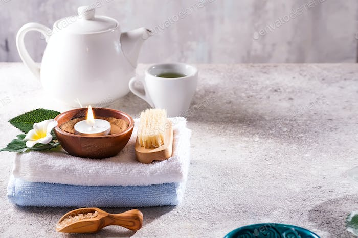 Spa resort therapy composition. Burning candles, towel, tea set and flower on a stone background