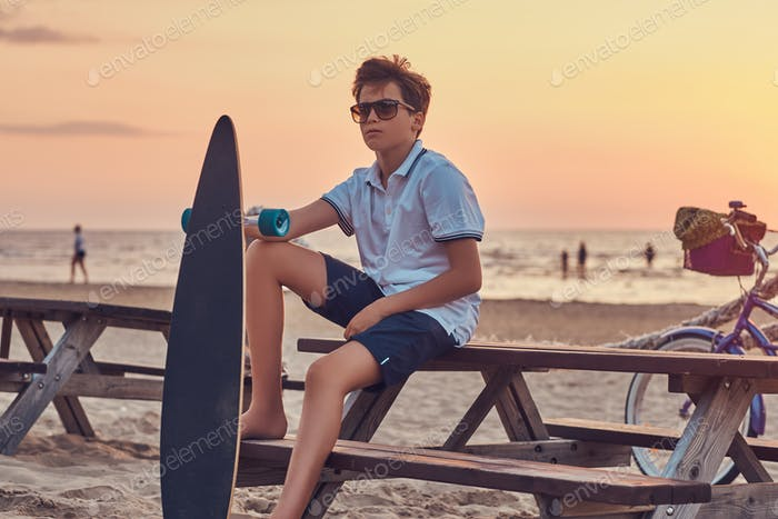 Young skater boy sitting on a bench against the background of a seacoast at the bright sunset.