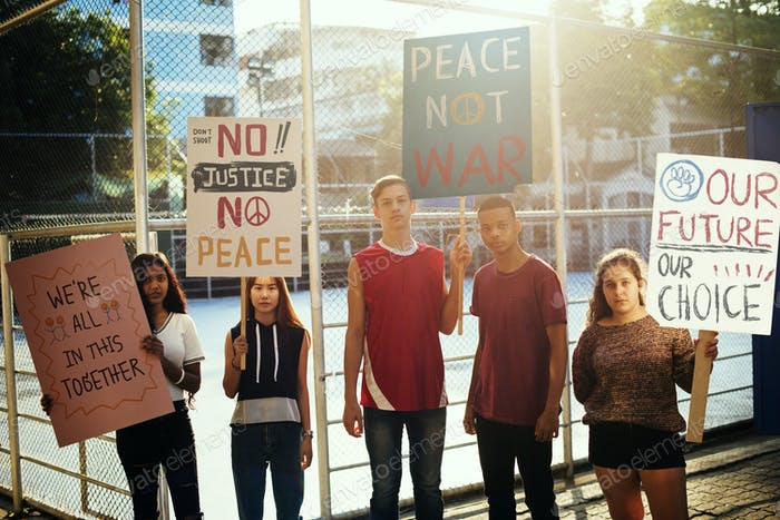 Group of teenagers protesting demonstration holding posters antiwar justice peace concept