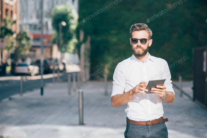 Knee figure of young handsome bearded businessman holding a tabl