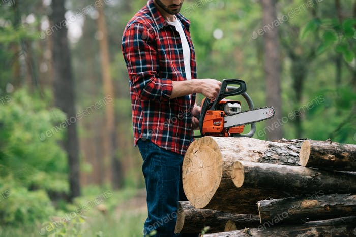 cropped view of lumberjack cutting round timbers with chainsaw in forest