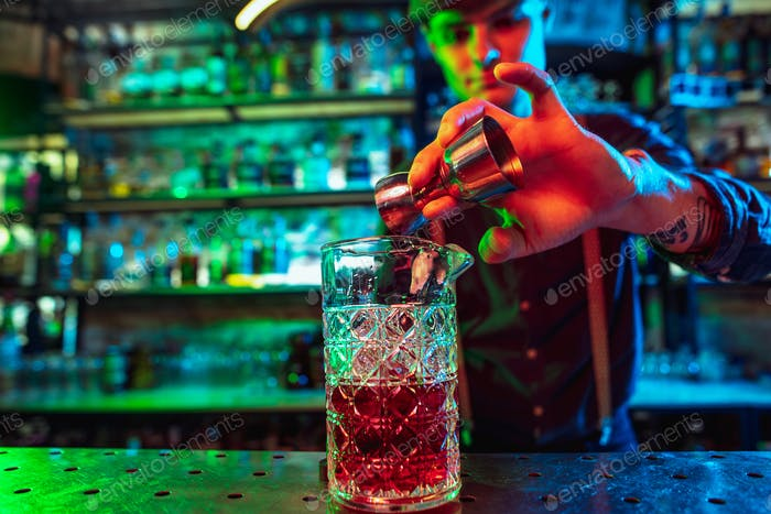 Barman finishes preparation of alcoholic cocktail with shot in multicolored neon light