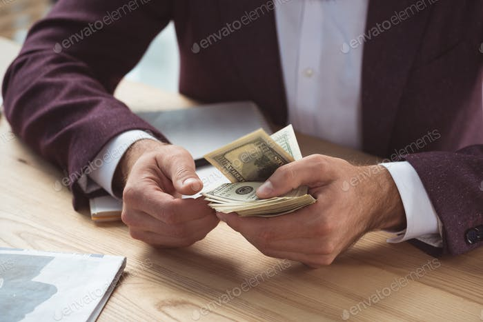 cropped view of businessman counting dollar banknotes, salary concept