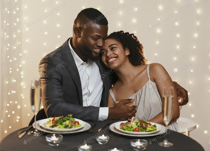 Handsome african man hugging his girlfriend while festive dinner