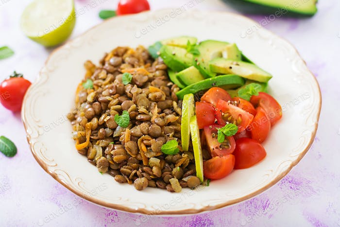 Diet menu. Healthy lifestyle. Lentils porridge and fresh vegetables - tomatoes and avocado on plate.