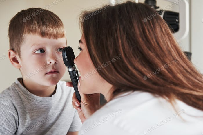 Boy have eye test with special little device. Concentrating on sight health
