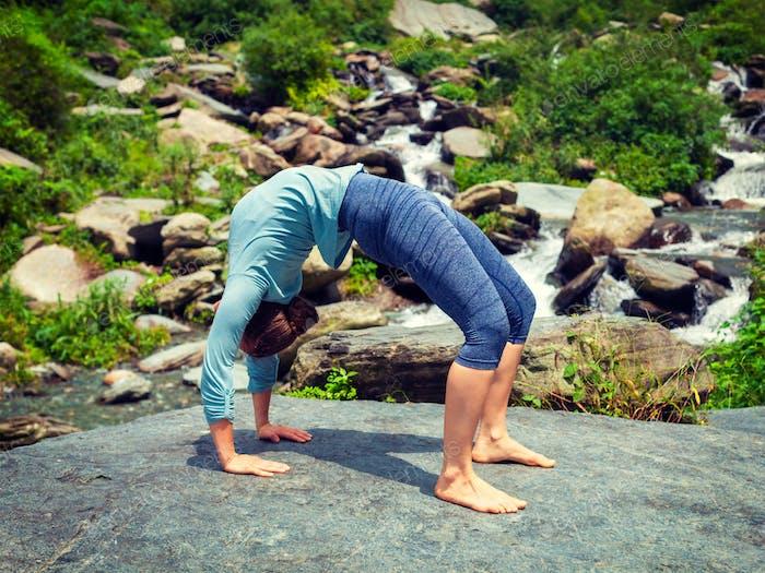 Woman doing Ashtanga Vinyasa Yoga asana Urdhva Dhanurasana  - up