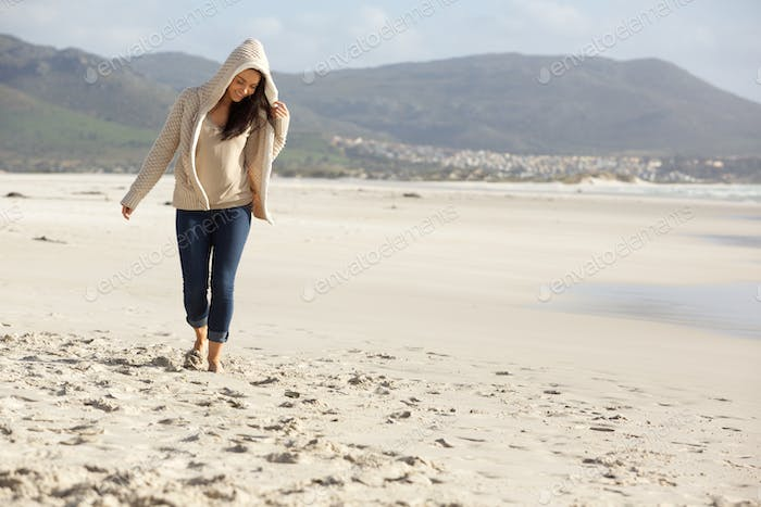 Happy young woman taking a walk by the sea shore