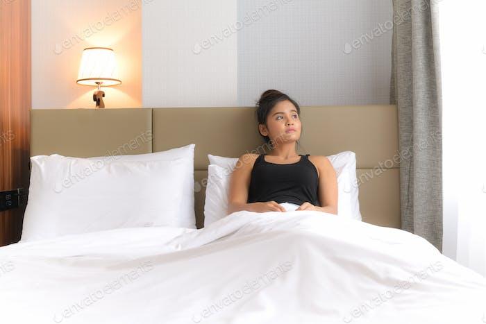 Schöne Frau im Bett Blick durch Fenster