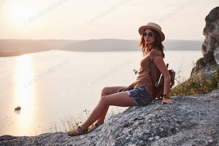 Senderismo mujer con mochila relajante en la parte superior del acantilado