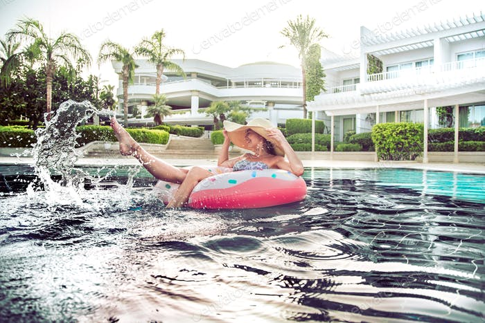 Summer holiday by the pool . Woman relaxes on an inflatable circle in the pool.