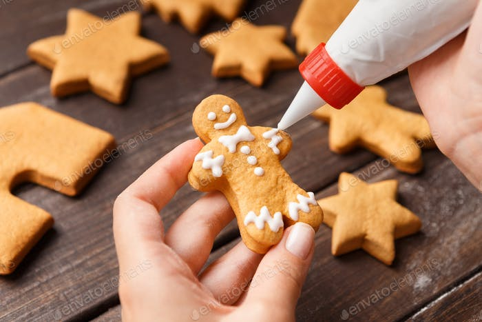 Confectioner decorating gingerman with royal icing, closeup