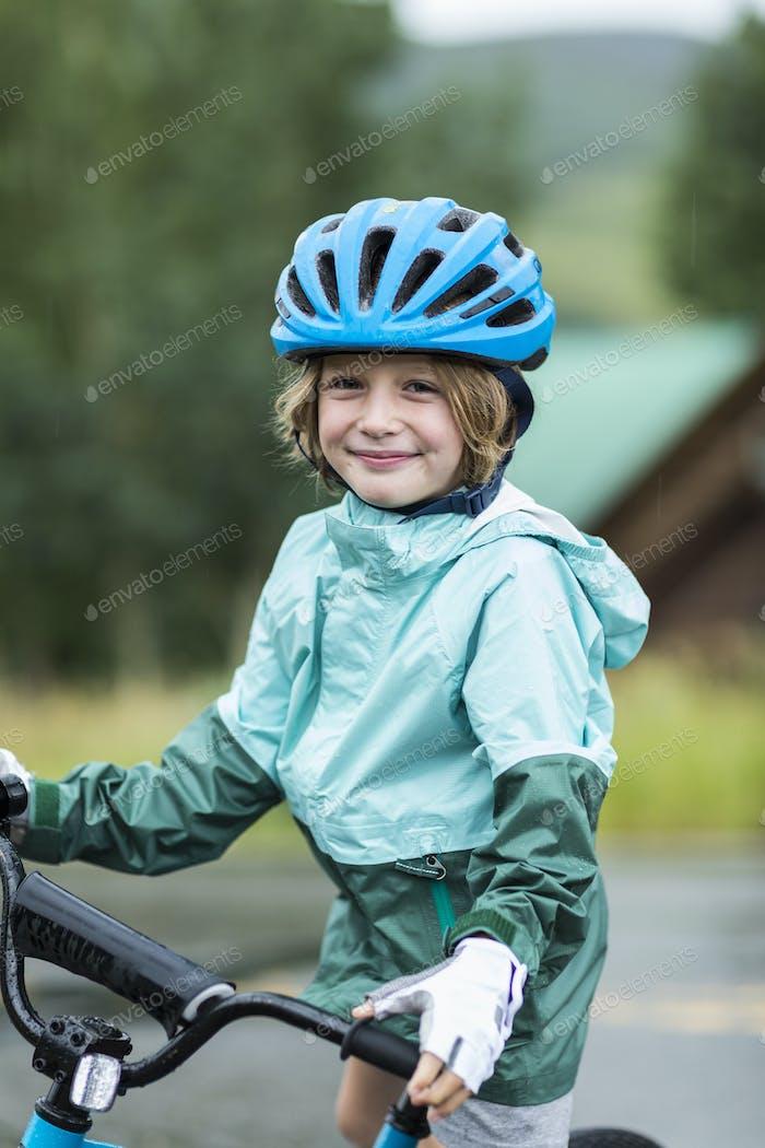 portrait of 5 year old boy wearing rain jacket, straddling his bike
