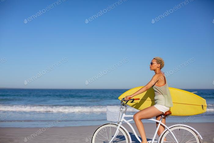 Seitenansicht der afrikanischen amerikanischen Frau mit Surfbrett sitzen auf dem Fahrrad am Strand in der Sonne