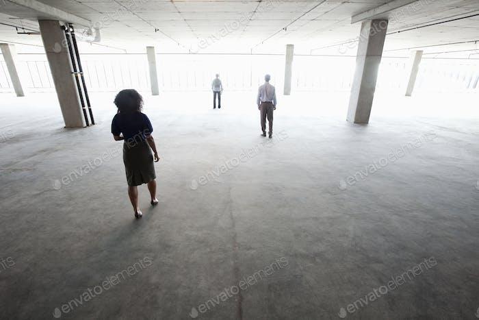 Business people walking toward windows in a large empty office raw space.