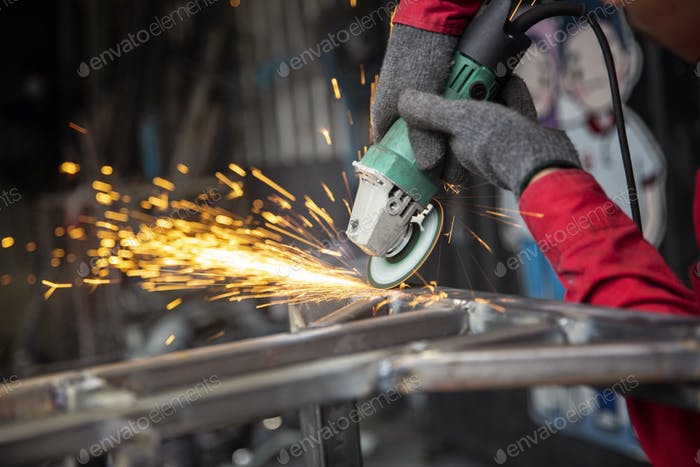 Welder used grinding stone on steel in factory with sparks.