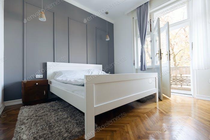 Interieur von weißen und grauen gemütlichen Schlafzimmer