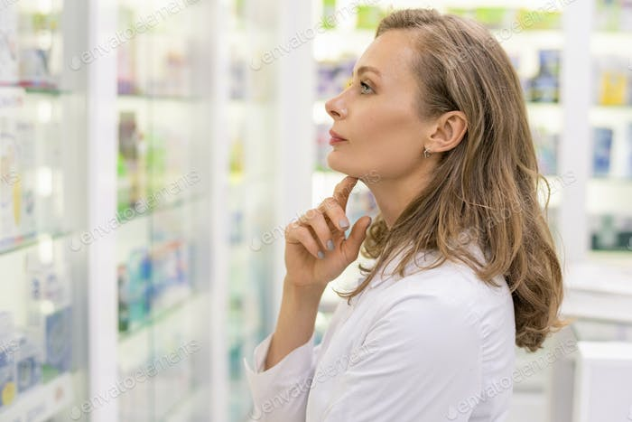 Young serious female pharmacist or consultant of contemporary drugstore