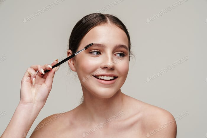 Image of joyful young shirtless woman using eyebrows brush and smiling
