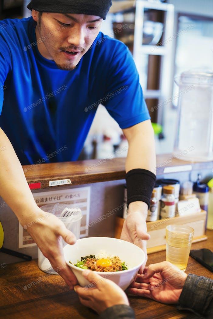 Der Ramen-Nudelladen. Ein Koch liefert eine Schüssel Ramen-Nudeln an einen Kunden.