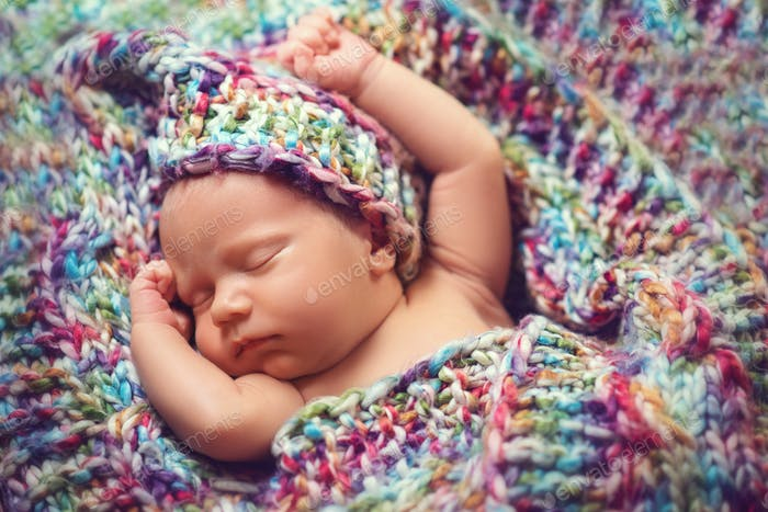 Newborn baby sleeps in a knitted scarf