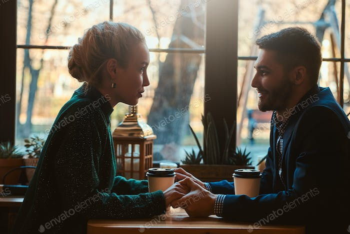 Romantic couple is sitting at cafe at their date