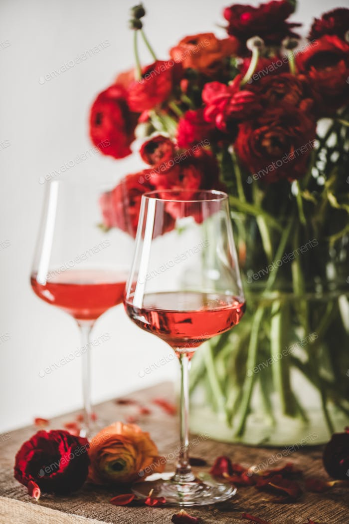 Rose wine in glasses and red spring flowers, selective focus