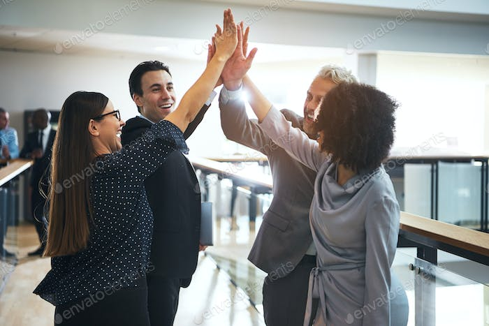 Cheerful multiethnic office team giving high five
