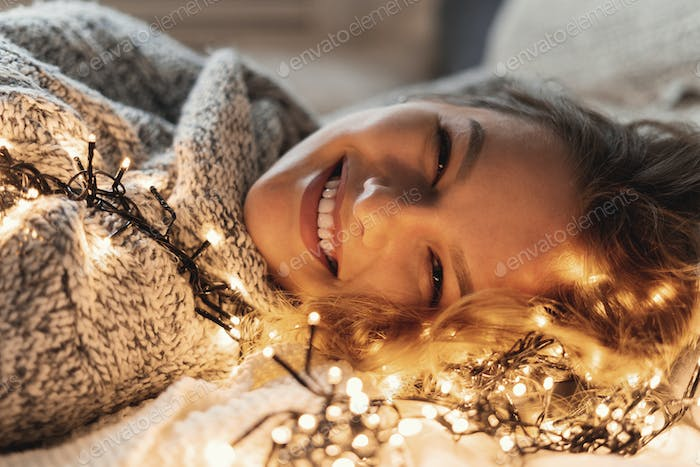 Portrait Smiling Woman With Beautiful Face Smiling, Lying In Bed With Lights In Her Hair