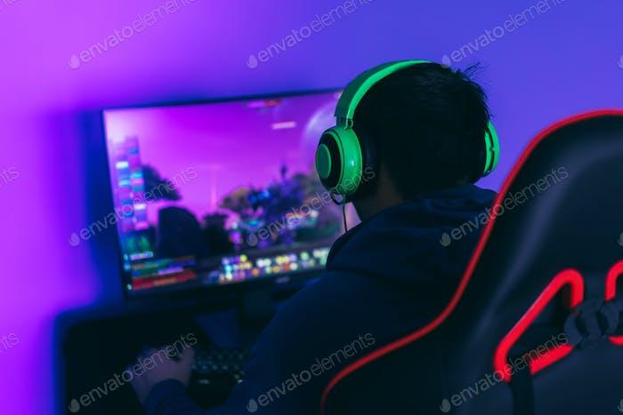 El tipo del jugador juega juegos de ordenador. Un pasatiempo moderno, jugar juegos de ordenador. Vista lateral