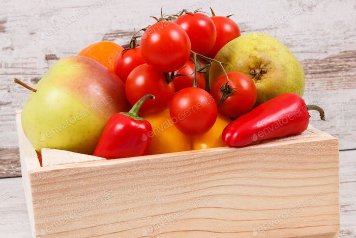 Fruits with vegetables in wooden box as healthy snack or dessert containing natural vitamins