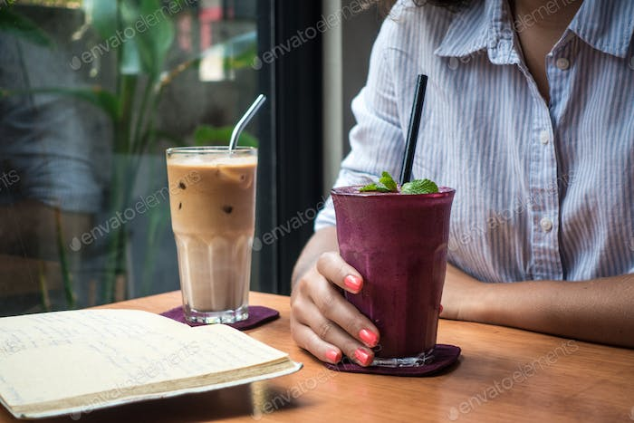 Young lady enjoying her drinks while journaling in a coffee shop