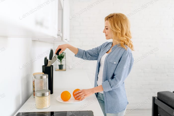 Woman preparing oranges, breakfast on the kitchen