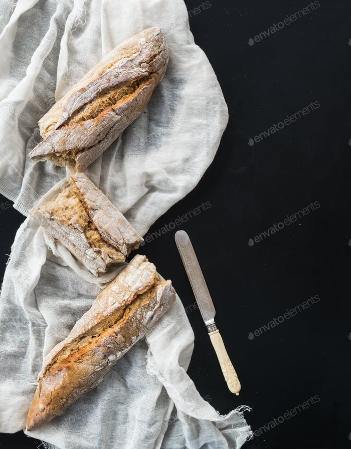 French baguette broken into pieces on a white kitchen towel with