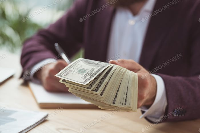 cropped view of businessman giving dollar banknotes, salary concept