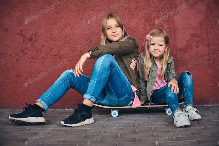 Zwei kleine Schwestern lehnten sich an eine Wand, während sie auf einem Skateboard an einem Brückenfußraum sitzen.