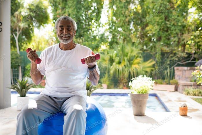 Porträt des Mannes, der Hanteln hält, während auf Fitness-Ball sitzt