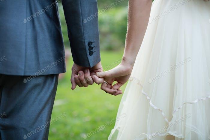 Wedding couple holding hands in garden