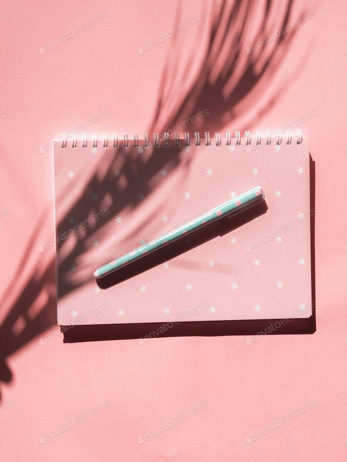 Rosa Notizbuch mit Stift und tropischem Pflanzenschatten