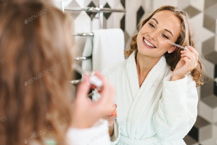 Smiling young blonde woman wearing bathrobe
