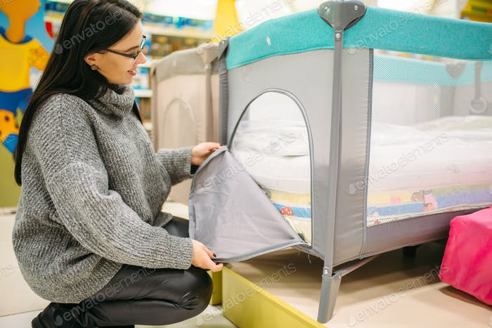 Pregnant woman buying cot in store