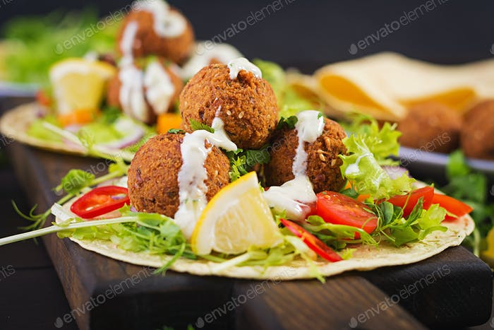 Tortilla wrap with falafel and fresh salad. Vegan tacos. Vegetarian healthy food.