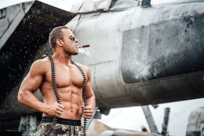 Naked muscular guy explores aircraft and smokes cigar